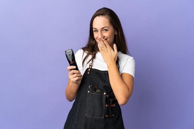 Junge friseurfrau über isoliertem hintergrund glücklich und lächelnd, den mund mit der hand bedeckend