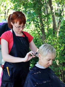 Junge friseurin, die der frau draußen im garten einen kurzen haarschnitt mit einer schere macht