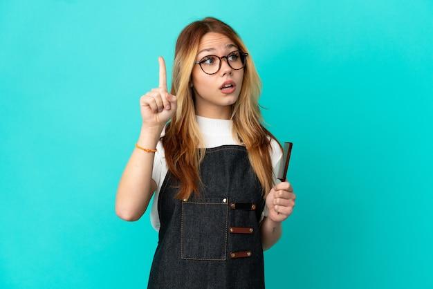 Junge friseurin über isoliertem blauem hintergrund, die beabsichtigt, die lösung zu realisieren, während sie einen finger hochhebt