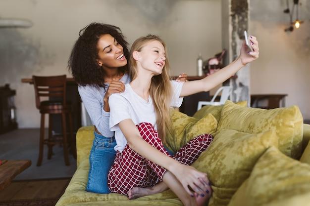 Junge fröhliche afroamerikanerfrau mit dunklem lockigem haar und hübsche frau mit blondem haar, die freudig fotos auf handy zusammen bei gemütlichem zuhause machen