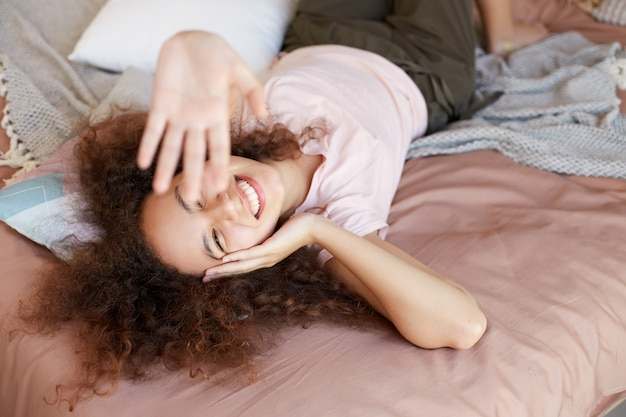 Junge fröhliche afroamerikanerin genießt den sonnigen tag zu hause, verbringt ihren freien tag und ruht sich zu hause aus, liegt auf dem bett und lächelt breit und berührt die wange.