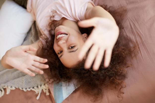 Junge fröhliche afroamerikanerin genießt den sonnigen tag zu hause, verbringt ihren freien tag und ruht sich zu hause aus, liegt auf dem bett und lächelt breit.
