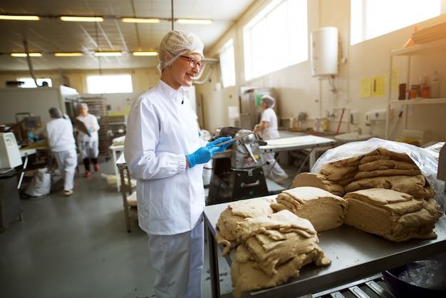 Junge fröhliche arbeiterin in sterilen tüchern, die eine tablette halten und die qualität der keksteigmischung vor der weiteren verarbeitung überprüfen.