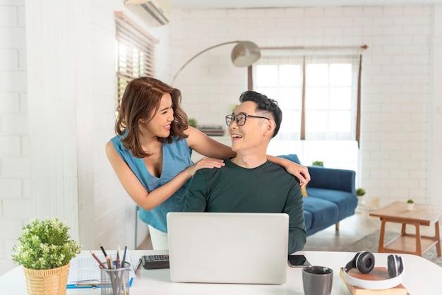 Junge fröhliche asiatische paarkollegen arbeiten mit laptop-computer drinnen im büro, das miteinander spricht.