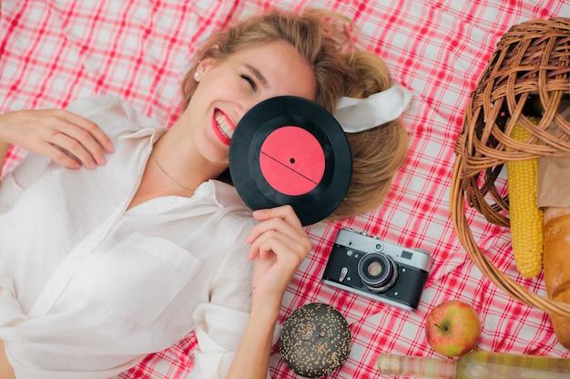 Junge fröhliche blonde frau in den vintage-kleidern, die schallplatte im gesicht halten, während auf picknicktischdecke im freien liegt. draufsicht