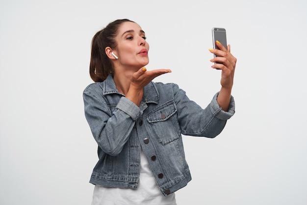 Junge fröhliche brünette dame trägt in weißem t-shirt und jeansjacken, hält smartphone und schickt kuss an den videochat. steht über weißem hintergrund.