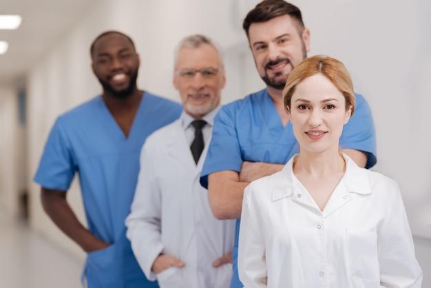 Junge fröhliche charmante krankenschwester, die verantwortung bei der arbeit genießt und im krankenhaus steht, während kollegen stehen