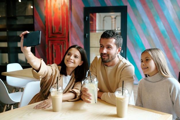 Junge fröhliche dreiköpfige familie, die nach dem einkaufen am tisch im café sitzt, milchcocktails genießt und selfie macht