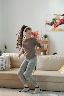 Junge fröhliche energische frau in aktivkleidung, die durch musik in kopfhörern tanzt, während sie durch couch steht