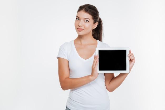 Junge fröhliche frau, die digitales tablet hält und das display nach vorne zeigt, isoliert auf weißer wand.