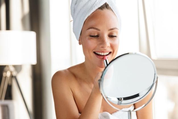 Junge fröhliche frau, die in weiße handtücher gehüllt ist und make-up macht, während sie nach der dusche in den spiegel schaut