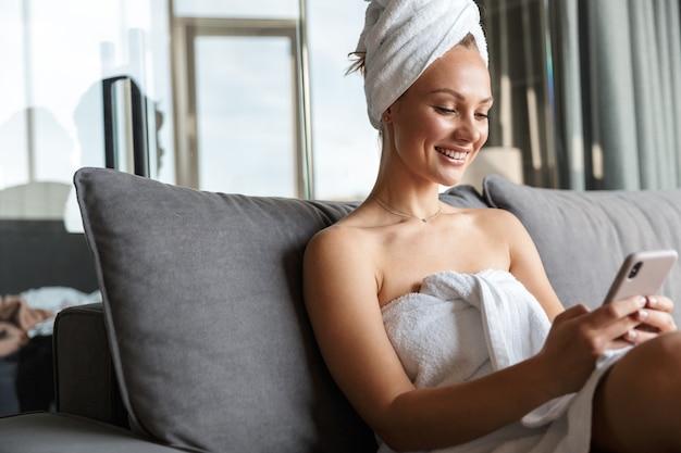 Junge fröhliche frau, die mit dem handy in weiße handtücher gehüllt ist, während sie nach der dusche im zimmer sitzt?