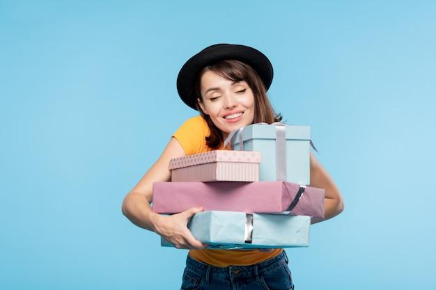 Junge fröhliche frau im hut, die stapel von verpackten geschenken umarmt, nachdem sie sie auf saisonalen verkauf gekauft haben