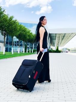 Junge fröhliche frau mit einem koffer. das von reisen und arbeiten