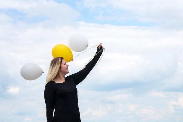 Junge fröhliche frau mit luftballons auf dem dach