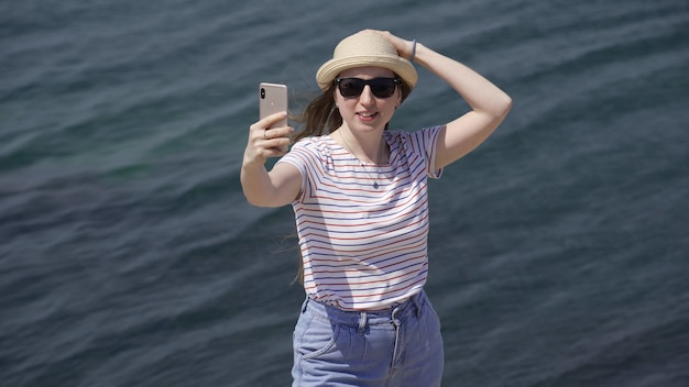 Junge fröhliche frau spricht videoanruf mit telefon auf see. die frau teilt ihre eindrücke von der reise und reise. 4k uhd