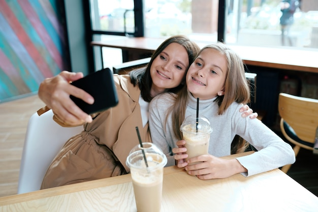 Junge fröhliche frau und ihre tochter in freizeitkleidung machen selfie, während sie sich im café ausruhen und leckere getränke haben