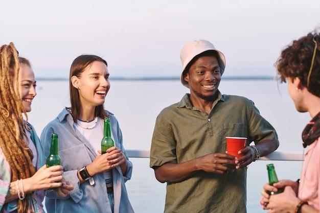 Junge fröhliche freunde mit getränken, die witze auf der sommerparty erzählen