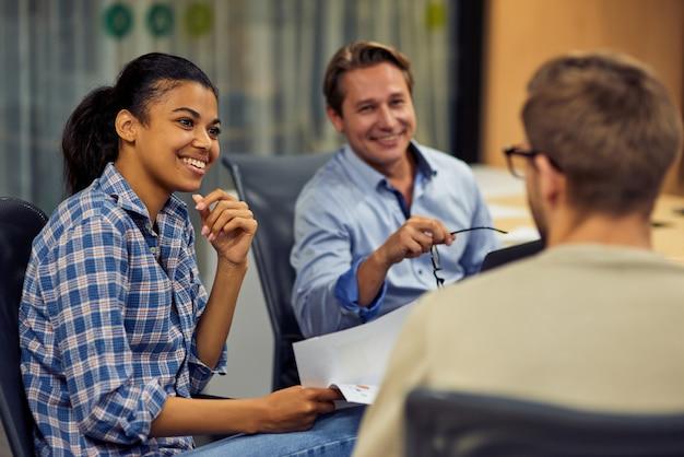Junge fröhliche gemischte büroangestellte, die im sitzen mit ihren kollegen über geschäfte diskutiert