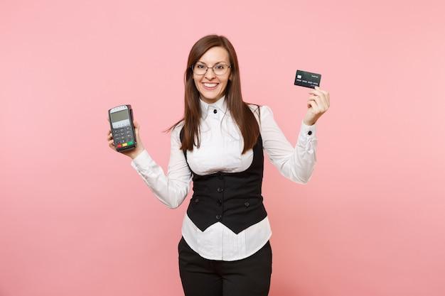 Junge fröhliche geschäftsfrau, die drahtloses modernes bankzahlungsterminal hält, um kreditkartenzahlungen zu verarbeiten und zu erwerben, schwarze karte einzeln auf rosafarbenem hintergrund. chefin. erfolg karriere reichtum.