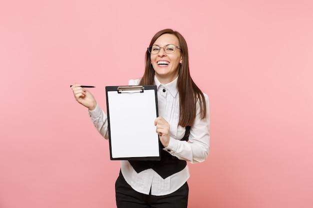 Junge fröhliche geschäftsfrau in gläsern, die stift auf zwischenablagetablette mit leerem leerem blattarbeitsplatzkopienraum lokalisiert auf rosa hintergrund zeigen. chefin. erfolg karriere reichtum. werbefläche.