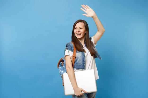 Junge fröhliche glückliche studentin mit rucksack winkende hand zur begrüßung, freunde treffen, die laptop-pc-computer isoliert auf blauem hintergrund halten. ausbildung an der hochschule. kopieren sie platz für werbung.