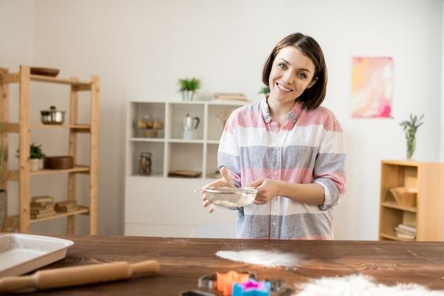 Junge fröhliche hausfrau, die mehl durch sieb über holztisch sieben, während teig für hausgemachtes gebäck vorbereitet