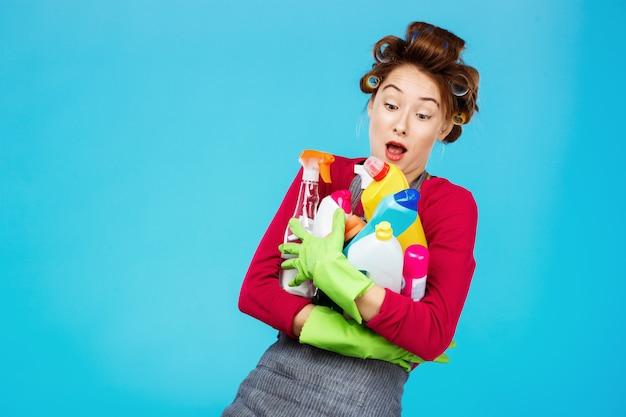 Junge fröhliche hausfrau in rosa und grau hält reinigungswerkzeuge