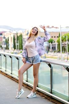 Junge fröhliche hübsche frau, die am europäischen platz reist und aufwirft und v geste und lachen zeigt, glücklicher tourist, sportliche kleidung, gesunder lebensstil.