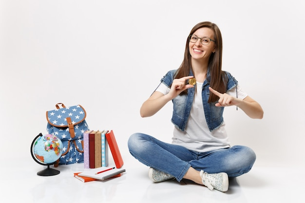 Junge fröhliche hübsche studentin mit brille, die mit dem zeigefinger auf bitcoin zeigt, sitzt in der nähe von globus, rucksack, schulbüchern isoliert