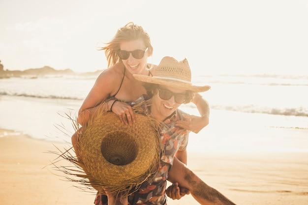 Junge fröhliche leute, die sich zu zweit mit einem mann amüsieren, tragen eine schöne frau - lachen zusammen und genießen den sonnigen urlaubstag am strand - romantik und liebeskonzept