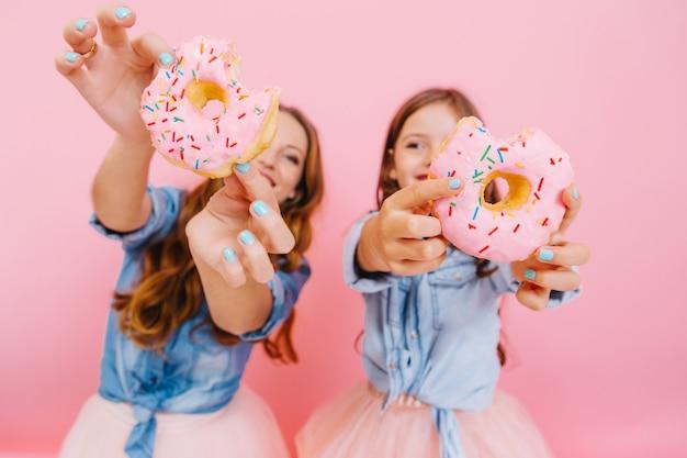 Junge fröhliche mutter und süße lächelnde tochter, die spaß mit leckeren donuts haben, die auf teeparty mit familie warten. kleines mädchen mit ihrer mutter zeigt donuts, die sie zusammen gekocht haben und lachen