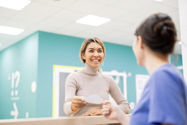 Junge fröhliche patientin, die der empfangsdame oder dem kliniker während der beratung mit ihr im krankenhaus medizinisches papier gibt
