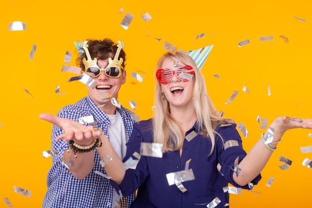 Junge fröhliche positive paar lustige brillen und eine papierkappe freuen sich und schreien auf einem gelben