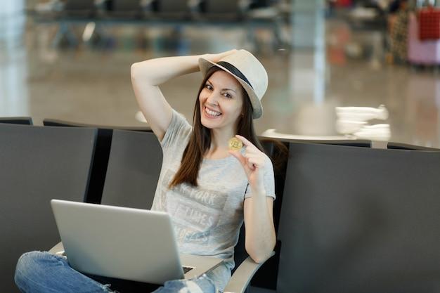 Junge fröhliche reisende touristenfrau mit hut, die am laptop arbeitet und bitcoin hält, der in der lobbyhalle am internationalen flughafen wartet?