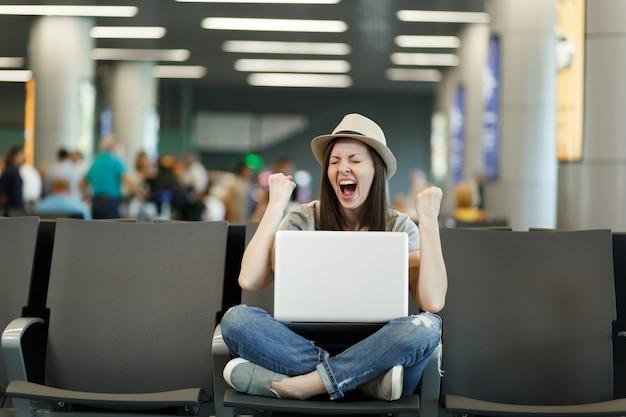 Junge fröhliche reisende touristenfrau mit laptop mit gekreuzten beinen macht gewinnergeste, wartet in der lobbyhalle am internationalen flughafen?