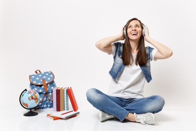 Junge fröhliche schöne studentin mit kopfhörern, die musik hört und in der nähe des globus-rucksack-schulbuchs sitzt, isoliert