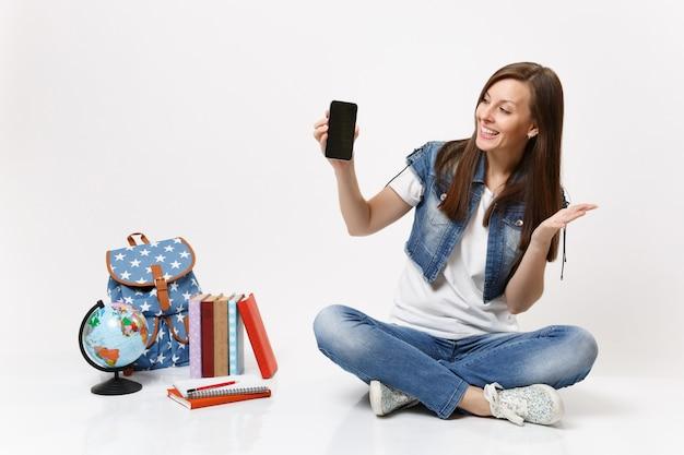 Junge fröhliche studentin hält handy mit leerer schwarzer leerer bildschirm verteilte hand sitzt in der nähe von globus, rucksack, isolierte schulbücher