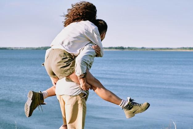 Junge fröhliche und liebevolle frau, die auf dem rücken ihres mannes oder freundes sitzt, während beide zeit am meer am sommertag genießen
