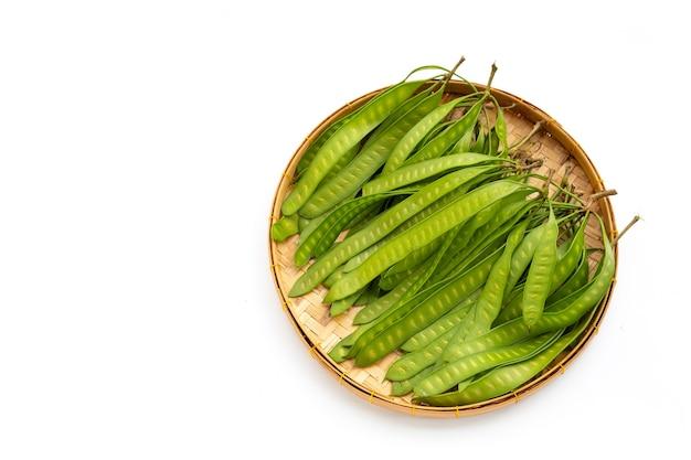 Junge frucht von leucaena leucocepphala im bambuskorb auf weißem hintergrund.