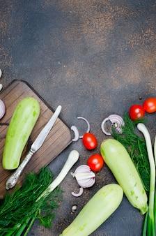 Junge frühlingszucchini, -tomaten, -kraut und -gewürze auf schwarzer oberfläche