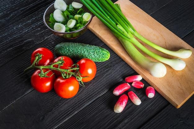 Junge frühlingszwiebeln auf einem schneidebrett. satz gemüse für eine salatdiät. salat kochen in der restaurantküche. kostenlose werbefläche.