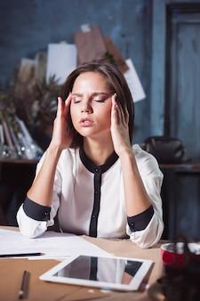 Junge frustrierte frau, die im loft-haus oder am schreibtisch vor dem laptop arbeitet und unter chronischen täglichen kopfschmerzen leidet Kostenlose Fotos