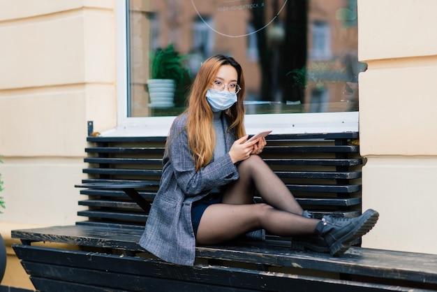 Junge fsian frau mit gesichtsmaske steht an einer inländischen straße. konzept der neuen normalität der pendler nach der covid-19-epidemie