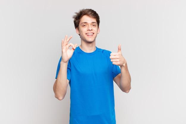 Junge fühlt sich glücklich, erstaunt, zufrieden und überrascht, zeigt in ordnung und daumen hoch, lächelt