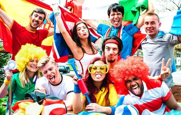 Junge fußballfans, die beim fußballspiel mit internationalen flaggen jubeln - glückliche menschen mit bunten t-shirts, die gemeinsam spaß im freien haben - sportmeisterschaftskonzept auf warmem, lebendigem filter