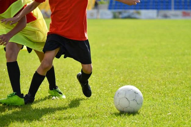 Junge fußballspieler spielen fußball im stadion