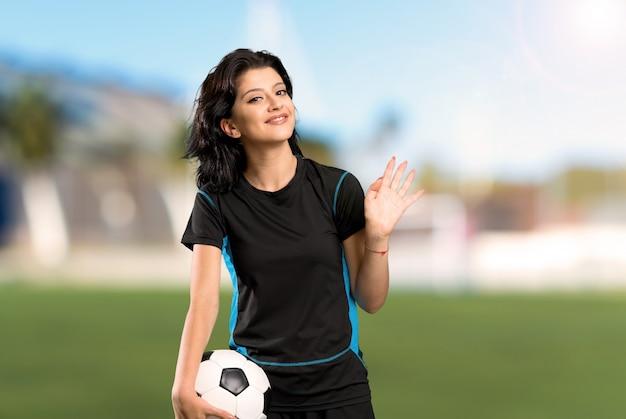 Junge fußballspielerfrau, die mit der hand mit glücklichem ausdruck an draußen begrüßt
