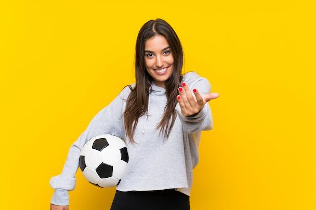 Junge fußballspielerfrau lokalisiert auf dem gelb, das einlädt, mit der hand zu kommen. schön, dass sie gekommen sind