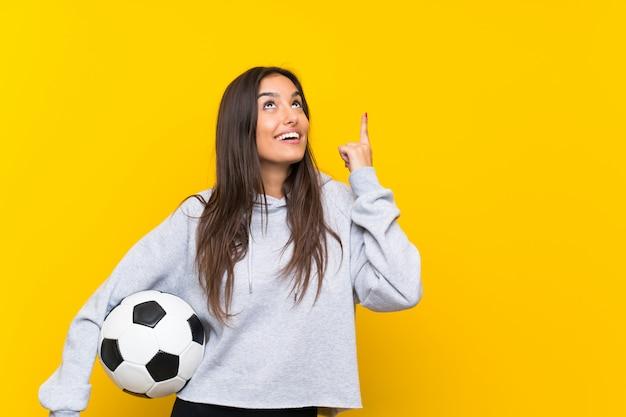 Junge fußballspielerfrau über der lokalisierten gelben wand, die beabsichtigt, die lösung zu verwirklichen
